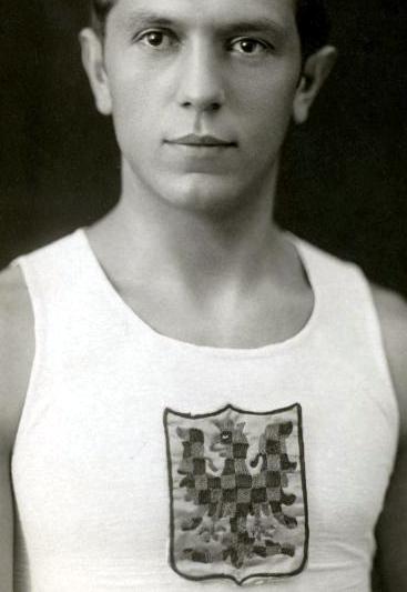Jan Koreis se zlato-červeně šachovanou orlicí atletického klubu Moravská Slávia (1. republika)